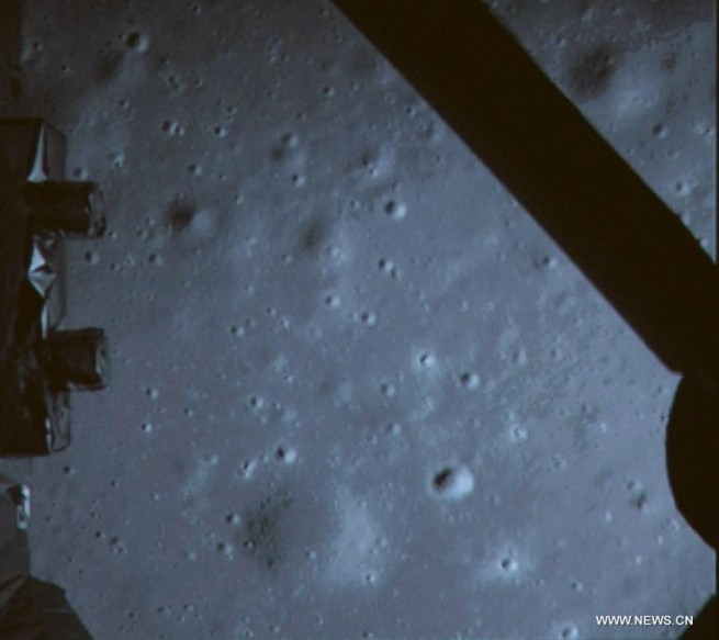 A photograph taken by the descent camera onboard Chang'e 3, moments prior to the lunar lander's historic soft-landing on the flat plains of Sinus Iridum. Photo Credit: Xinhua.net/CCTV