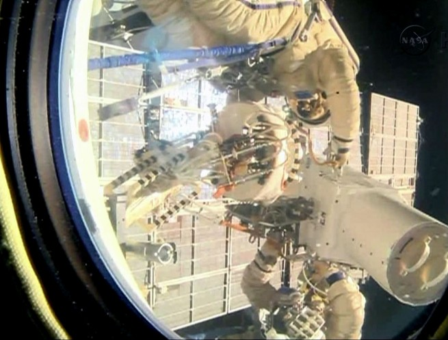 Spacewalkers Oleg Kotov and Sergey Ryazanskiy remove the high resolution camera they installed earlier during Friday's spacewalk. Photo Credit: NASA