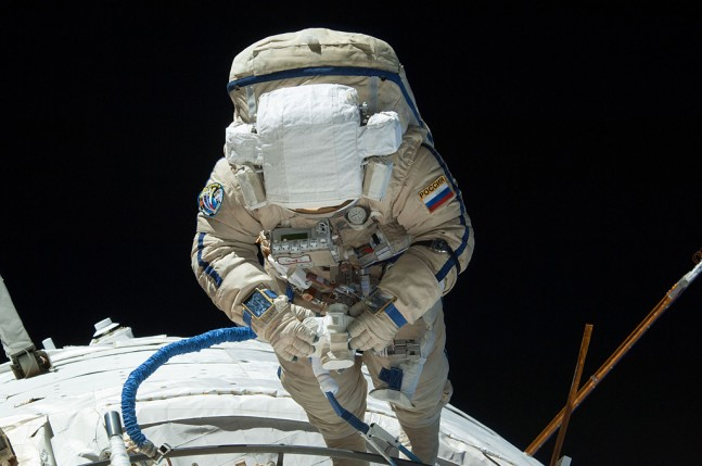 A cosmonaut inspecting his work as he moves around the Zvezda module during spacewalk #35, on August 22, 2013. Photo Credit: CNW Group/UrtheCast Corp