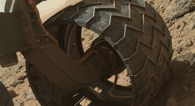 The left-front wheel of NASA's Curiosity Mars rover shows dents and holes in this photo taken during the 469th Martian day, or sol, of the rover's work on Mars (Nov. 30, 2013).  Photo Credit: NASA/JPL