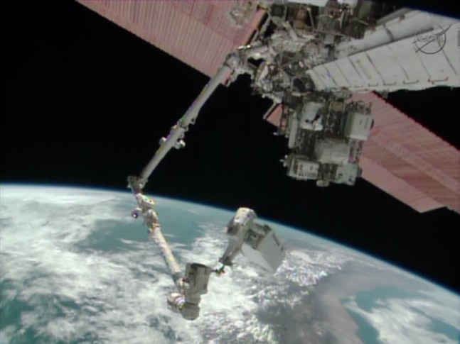 Astronaut Mike Hopkins rides the Canadarm2 carrying the 780-pound ammonia pump module as the International Space Station flies over South America. Image Credit: NASA TV
