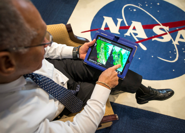 "NASA Administrator Charles Bolden explores ""Images of Change,"" a NASA application that allows users to view ""before and after"" images of the impact of human activities, a changing climate and natural disasters on Earth, Monday, Dec. 2, 2013, at NASA Headquarters in Washington. The application is available free for iOS devices. More images can be found at http://climate.nasa.gov  Photo Credit: NASA/Bill Ingalls"