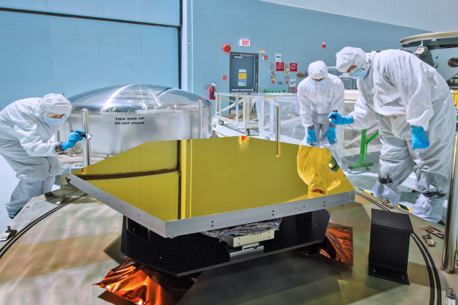 In this photo, NASA engineers and technicians inspect one of the James Webb Space Telescope's mirror segments which had been delivered prior to the final shipment of segments which arrived last week. Photo Credit: Chris Gunn / NASA GSFC