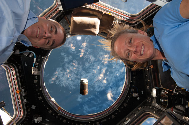 "NASA astronauts Chris Cassidy and Karen Nyberg, both Expedition 36 flight engineers, are pictured near the windows in the International Space Station's Cupola as the unpiloted Japanese ""Kounotori"" H2 Transfer Vehicle-4 (HTV-4) approaches the station (visible at center)."