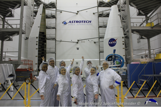 NASA Launch Services Program and ULA staff pose in front of the fairing which will protect TDRS L through ascent. Photo Credit: Jason Rhian / SpaceFlight Insider