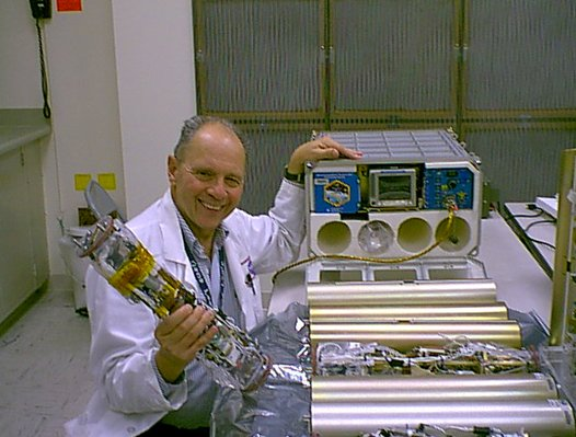 Dr. Dennis Morrison poses with the Microencapsulation Electrostatic Processing System flight hardware that was used on the International Space Station to produce microcapsules for cancer treatment delivery.  Photo Credit: NASA