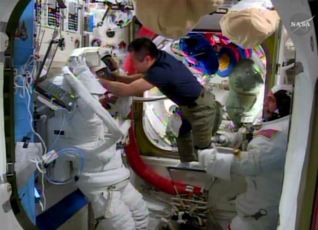 Astronauts Kochi Wakata helping Steve Swanson try out his suit in prep for upcoming spacewalk. Image Credit: NASA TV
