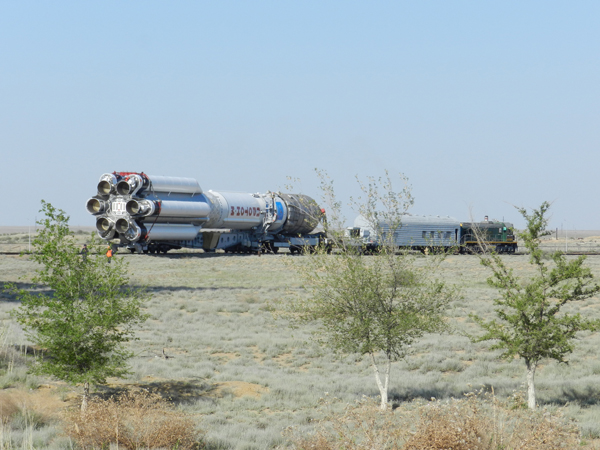 The Proton M rocket is led by rail to the Launch Complex at the Baikonur Cosmodrome. Photo Credit: Khrunichev