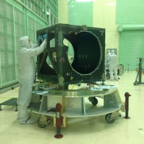An engineer checks ICESat-2's box structure, shortly after its arrival in a NASA clean room in May. Over the next two years, engineers and technicians will attach electronics, optics, lasers, a telescope and more to the box, testing its function at each step. Image Credit:  NASA's Goddard Space Flight Center/Kate Ramsayer