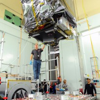 A crew guides the ATLAS box structure onto the shaker table in a vibration chamber at Goddard's Integration and Testing Facility. The box structure went through a number of tests, including thermal cycling and acoustic, before being delivered for Integration and Testing. Image Credit:  NASA's Goddard Space Flight Center/Debbie McCallum