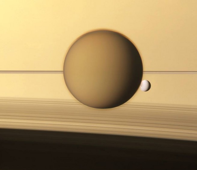 Titan can be seen here with another of Saturn's moons orbiting the gas giant. Image Credit: NASA / JPL