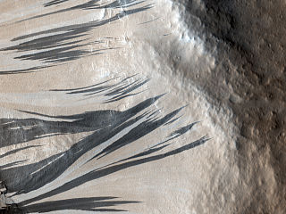 An example of dark slope streaks, or recurring slope lineae, which are more likely to be formed by briny liquid water. Photo Credit: NASA/JPL-Caltech