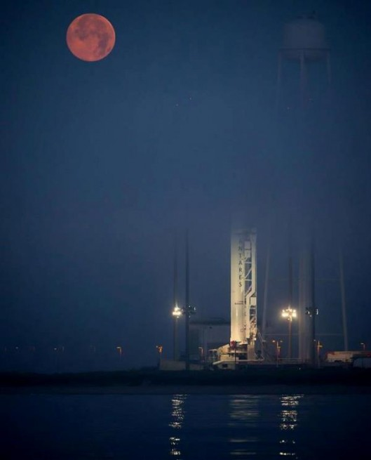 "Bathed in the light of a ""Super Moon"" Antares awaits flight. Photo Credit: Bill Ingalls / NASA"