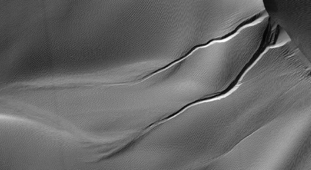 Linear gullies on Martian sand dunes, possibly cause by blocks of carbon dioxide ice sliding downhill. Photo Credit: NASA/JPL-Caltech/Univ. of Arizona