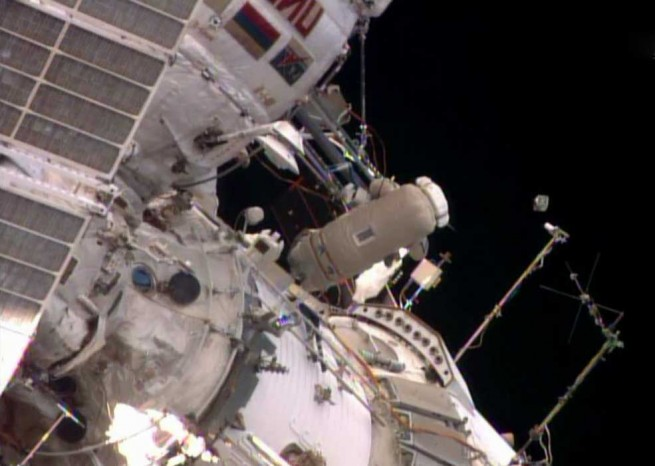 Flight Engineer Oleg Artemyev deploys the Chasqui 1 nanosatellite outside the Pirs docking compartment near the beginning of Monday's spacewalk. Photo Credit: NASA TV