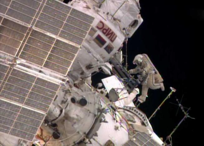 While Flight Engineer Alexander Skvortsov retrieves hardware inside the International Space Station's Pirs airlock, Flight Engineer Oleg Artemyev stretches his legs. Photo Credit: NASA TV