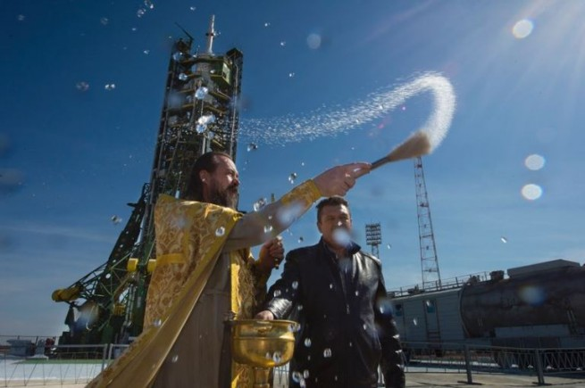 An Orthodox priest blesses members of the media at the Baikonur Cosmodrome launch pad on Wednesday, Sept. 24, 2014, in Kazakhstan.  Launch of the Soyuz rocket is scheduled for Sept. 26 and will carry Expedition 41 Soyuz Commander Alexander Samokutyaev of the Russian Federal Space Agency (Roscosmos), Flight Engineer Barry Wilmore of NASA, and Flight Engineer Elena Serova of Roscosmos into orbit to begin their five and a half month mission on the International Space Station. Photo Credit: Aubrey Gemignani / NASA