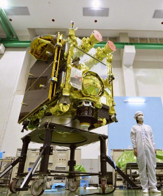 A technician standing next to the Hayabusa spacecraft helps to provide a sense of scale as to the size of the probe. Photo Credit: The Japan TImes