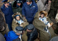 Ed Lu (left) and Yuri Malenchenko staying warm in chairs after extraction from Soyuz TMA-2. Photo Credit: NASA/Bill Ingalls
