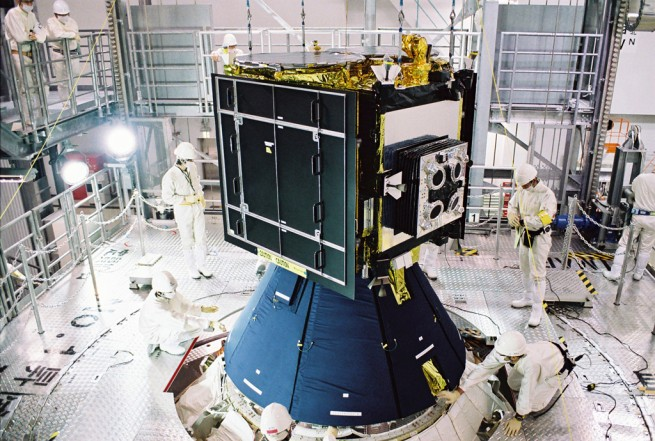 The Hayabusa 2 spacecraft as it undergoes payload fairing assembly. Photo Credit: JAXA