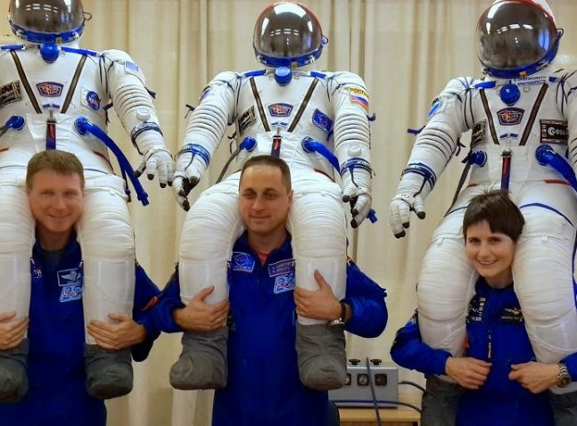 The crew of Expedition 42 poses for a photo with their spacesuits. Photo Credit: Samantha Cristoforetti / Twitter posted on SpaceFlight Insider