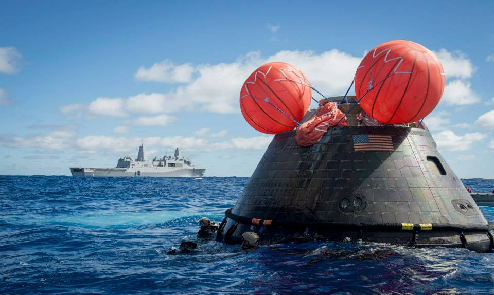 Navy Divers, assigned to Explosive Ordnance Disposal Mobile Unit 11 (EODMU11) and Mobile Dive and Salvage Company 11‐7, attach a towing bridle to NASA's Orion Crew Module. The amphibious transport dock USS Anchorage (LPD 23) is currently conducting the first exploration flight test (EFT) for the NASA Orion Program. EFT-1 is the first at-sea testing of the Orion Crew Module using a Navy well deck recovery method. (U.S. Navy Photo by Mass Communication Specialist 1st Class Gary Keen posted on SpaceFlight Insider