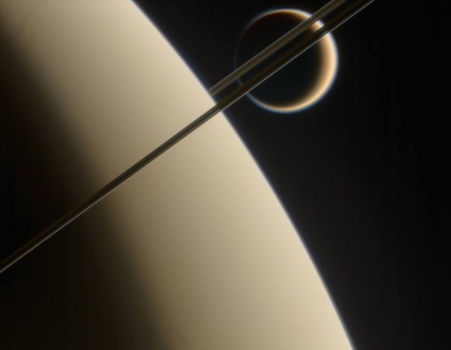Saturn with its moon Titan in the background NASA JPL photo posted on SpaceFlight Insider