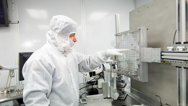 Researcher in the clean room with the samples collected by the Stardust spacecraft as posted on Spaceflight Insider.