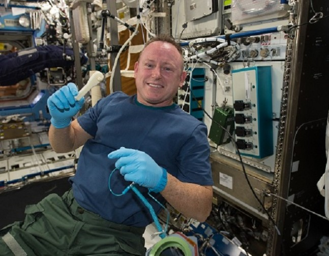Astronaut Butch Wilmore holds a 3D printed wrench, created on the station's 3D printer as seen on Spaceflight Insider