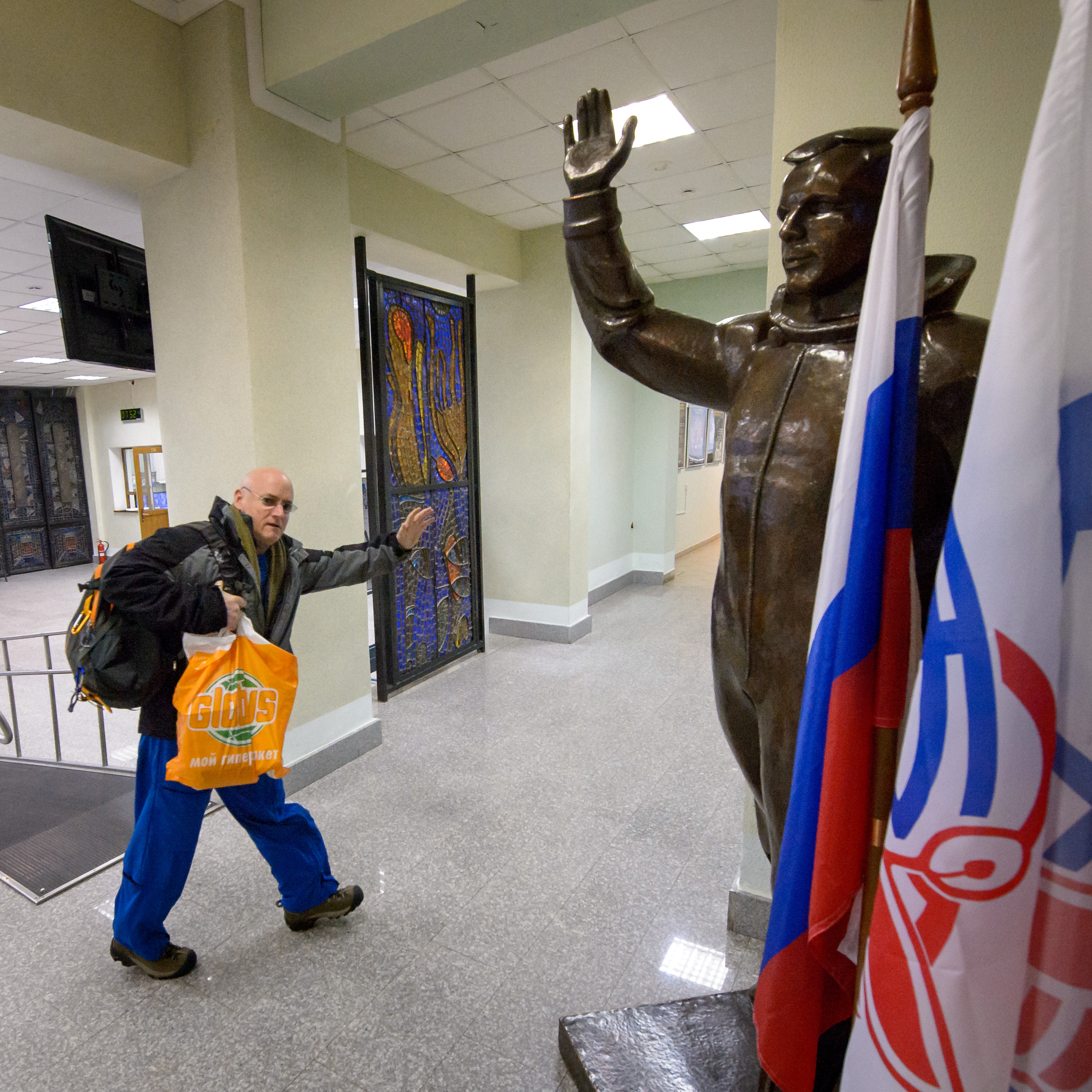 NASA Astronaut Scott Kelly waves hello as he passes a statue of Russian Cosmonaut Yuri Gagarin Thursday, March 5, 2015 at the Gagarin Cosmonaut Training Center (GCTC) Soyuz training facility in Star City, Russia