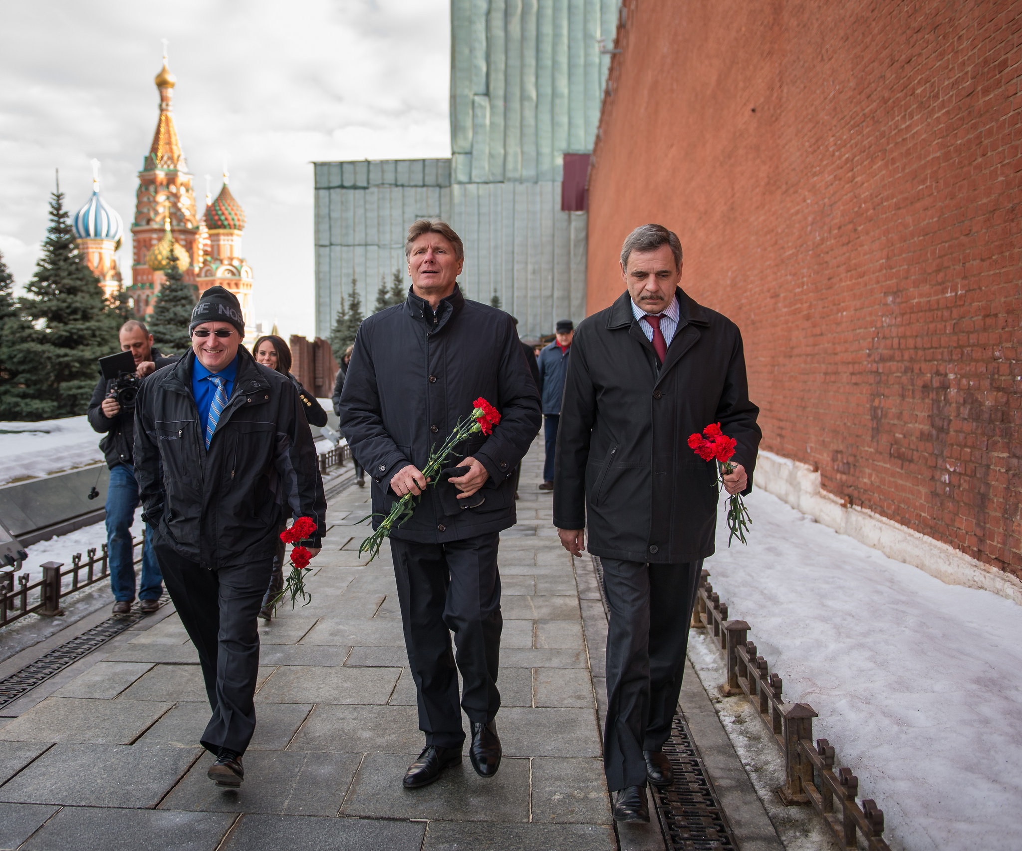 Expedition 43 NASA Astronaut Scott Kelly, left, Russian cosmonaut Gennady Padalka of the Russian Federal Space Agency (Roscosmos), center, and Russian cosmonaut Mikhail Kornienko of Roscosmos walk along the Kremlin Wall in Red Square to leave roses at the site where Russian space icons are interred as part of traditional pre-launch ceremonies, Friday, March 6, 2015, Moscow, Russia