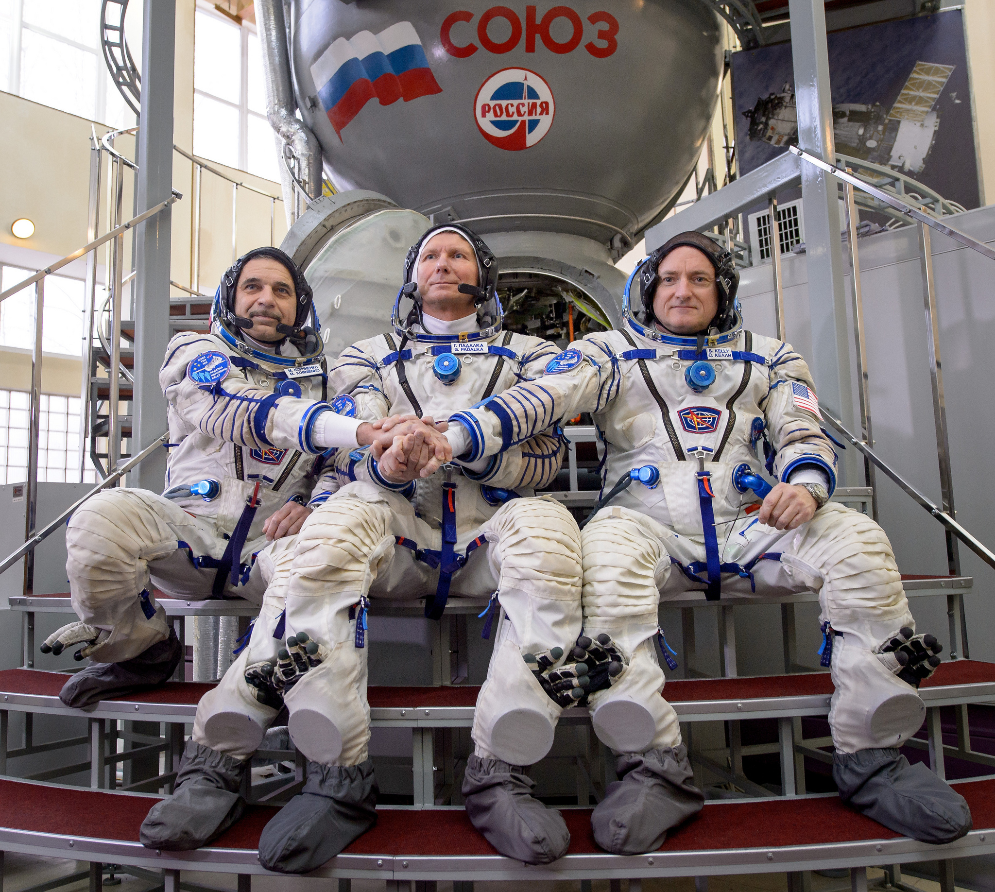 Expedition 43 Russian cosmonaut Mikhail Kornienko of the Russian Federal Space Agency (Roscosmos), left, Russian cosmonaut Gennady Padalka of Roscosmos, center, and NASA Astronaut Scott Kelly pose for a photograph outside a Soyuz simulator during the second day of qualification exams, Thursday, March 5, 2015 at the Gagarin Cosmonaut Training Center (GCTC) in Star City, Russia