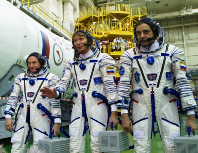 NASA astronaut Scott Kelly (left), Russian Space Agency (Roscosmos) cosmonauts Gennady Padalka (center) and Mikhail Kornienko (right) standing next to the Soyuz FG launch vehicle at the Spacecraft Processing Facility in Baikonur. Photo Credit: gctc.ru