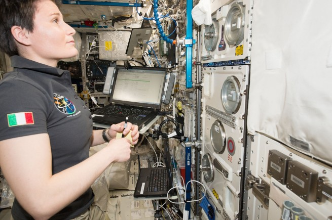 Samantha Cristoforetti, first Italian woman in space, Expedition 43 flight engineer aboard the International Space Station, is seen working on a science experiment that includes photographic documentation of Cellular Responses to Single and Combined Space Flight Conditions
