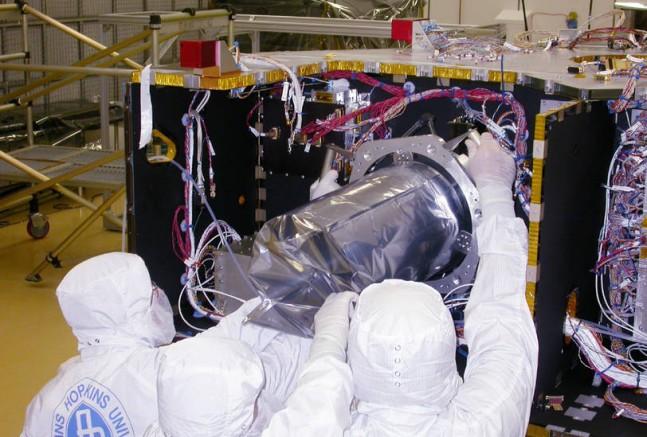 Technicians installing the Long Range Reconnaissance Imager (LORRI) on NASA's New Horizons spacecraft in 2005. Photo Credit: NASA