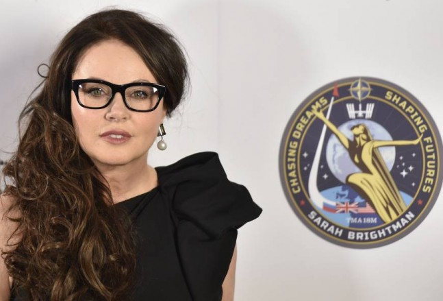 Sarah Brightman poses for photographs after speaking about her travel to the International Space Station, at a news conference in central London.