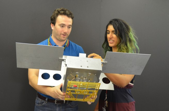Engineers holding a mockup of the MarCO Cubesat