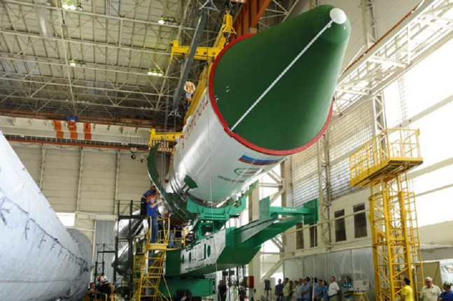 Orbital module containing Progress M-28M spacecraft is being integrated with the Soyuz-U launch vehicle in the processing facility