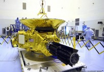 In the clean room at KSC's Payload Hazardous Servicing Facility, technicians prepare the New Horizons spacecraft for a media event.
