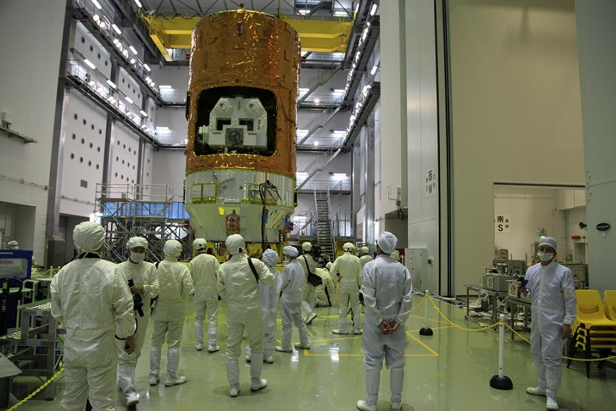 A crowd of media reporters photograph the fully integrated HTV-5 spacecraft at the Tanegashima Space Center