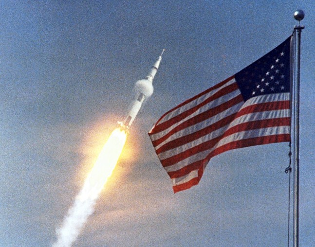 Apollo 11 Saturn V rocket lifts off from Kennedy Space Center Launch Complex 39A July 16 1969 in front of U.S. flag NASA photo posted on SpaceFlight Insider
