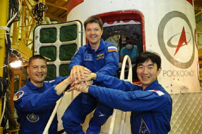 NASA astronaut Kjell Lindgren (left), Russian cosmonaut Oleg Kononenko (center), and JAXA astronaut Kimiya Yui (right) pose in front of the Soyuz TMA-17M spacecraft and a Soyuz-FG rocket.