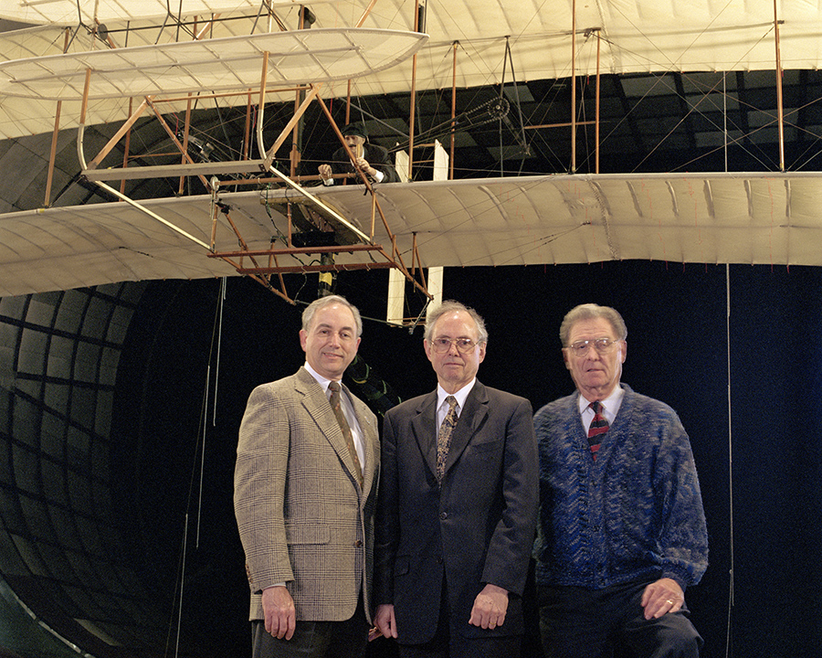 "Bill Berry, former Ames Deputy Director, Harry McDonald, former Ames Director and John W. ""Jack"" Boyd, Senior Advisor to the Ames Center Director in the National Full-Scale Aerodynamics Complex (NFAC) wind tunnel in front of a full-scale replica of the 1903 Wright 'Flyer' prior to testing. Photo Credit: NASA Ames, Tom Trower"