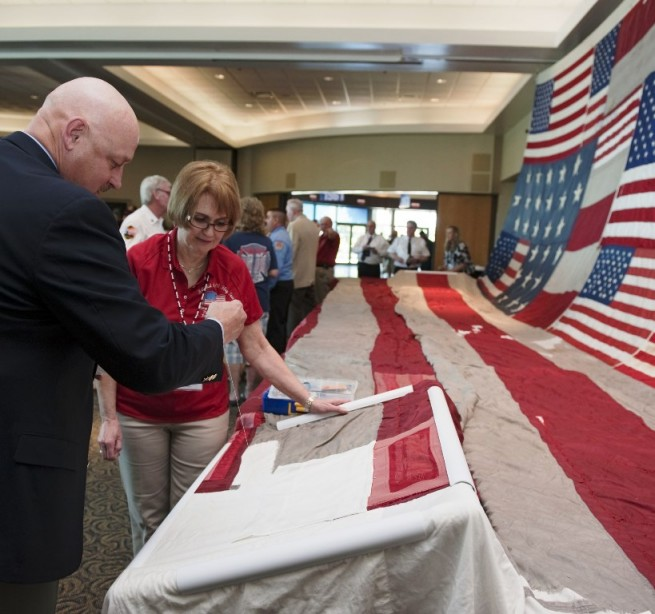 """Joe Dowdy, Kennedy Space Center's special operations manager adds stitches to Florida's contribution of the """"National 9/11 Flag"""" during an event held on Feb. 18. Photo Credit: Kim Shiflett / NASA"""