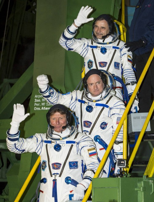 Expedition 43 Russian Cosmonaut Mikhail Kornienko of the Russian Federal Space Agency (Roscosmos), top, NASA Astronaut Scott Kelly, center, and Russian Cosmonaut Gennady Padalka of Roscosmos wave farewell as they board the Soyuz TMA-16M spacecraft ahead of their launch to the International Space Station, Friday, March 27, 2015 in Baikonor, Kazakhstan. As the one-year crew, Kelly and Kornienko will return to Earth on Soyuz TMA-18M in March 2016. Photo Credit: Bill Ingalls / NASA
