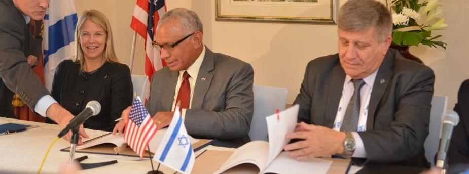 NASA Administrator Charles Bolden (center) and Israel Space Agency Director General Menachem Kidron (right) sign cooperation agreement at the International Astronautical Congress held in Jerusalem, Oct. 13, 2015