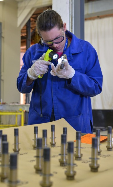 Jessica Widrick, joints and seals design engineer at Orbital ATK, inspects igniter bolts and seals after the static test of the first five-segment qualification motor for NASA's Space Launch System. Photo Credit Orbital ATK posted on SpaceFlight Insider