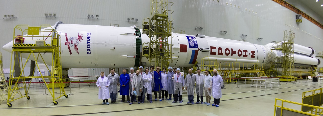 Some of the team at Baikonur who are preparing the ExoMars 2016 spacecraft for launch, pictured in front of the Proton rocket. The Trace Gas Orbiter and the entry, descent and landing demonstrator module, called Schiaparelli, are inside the fairing (with the ExoMars logo).