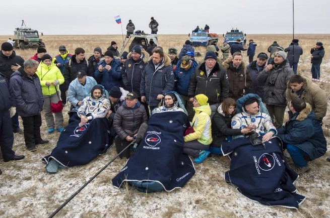 Russian cosmonauts Mikhail Kornienko, left, Sergey Volkov of Roscosmos, center, and Expedition 46 Commander Scott Kelly of NASA, rest in a chairs outside of the Soyuz TMA-18M spacecraft just minutes after they landed in a remote area near the town of Zhezkazgan, Kazakhstan on Wednesday, March 2, 2016 (Kazakh time). Kelly and Kornienko completed an International Space Station record year-long mission to collect valuable data on the effect of long duration weightlessness on the human body that will be used to formulate a human mission to Mars. Volkov returned after spending six months on the station. Photo Credit: Bill Ingalls / NASA
