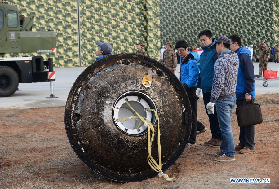 Scientific personnel works at the landing area of the re-entry capsule of China's first retrievable microgravity satellite Shijian 10 in Siziwang Banner, north China's Inner Mongolia Autonomous Region, Apr. 18, 2016.